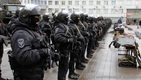 Members of the Russian SOBR stand in formation, dressed in black with helmets, and heavily armed.