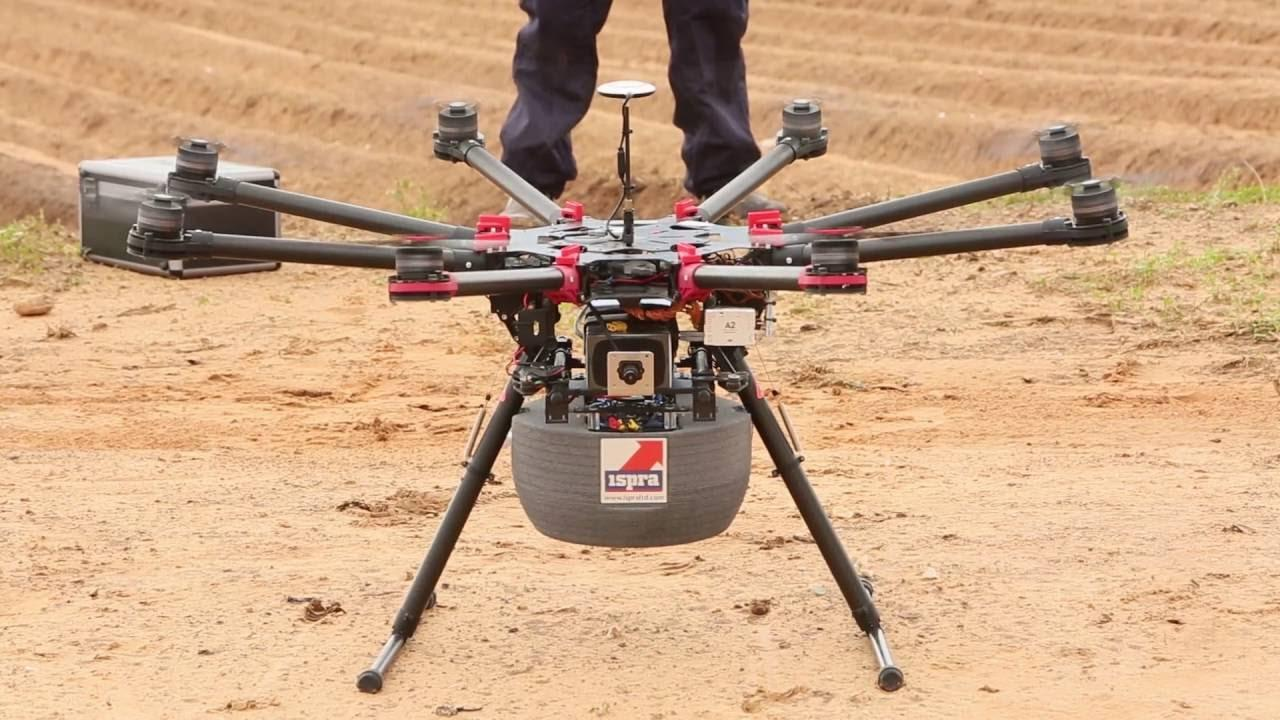 "A drone sits on the ground. It has long legs and six arms with rotors. Underneath is a grey box with the word ""ISPRA"" on the front"