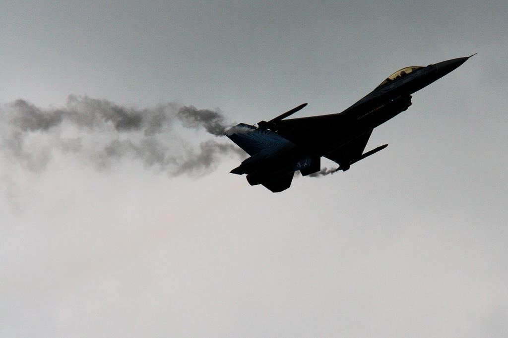 An F16 fighter jet sillhouetted against the sky