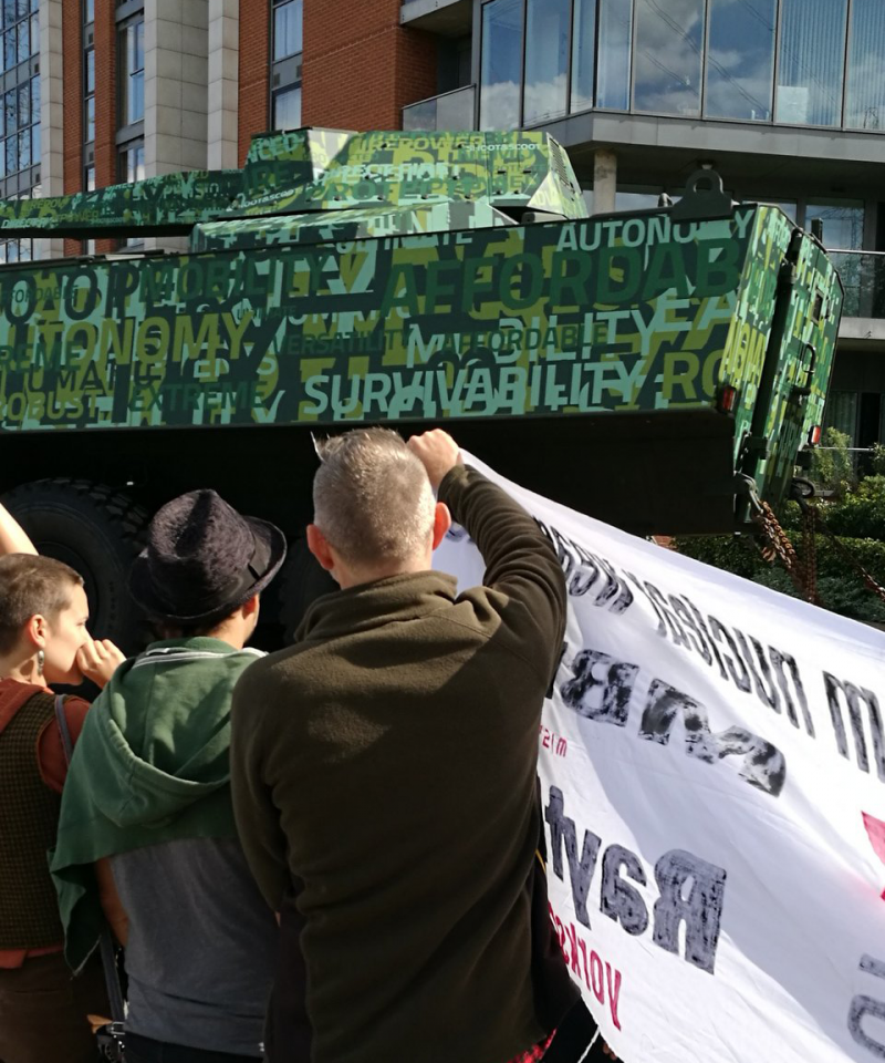 A tank entering the DSEI arms fair, covered in marketing slogans. In front stand a crowd holding banners