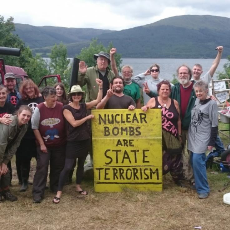 Gathering of people at the Coulport Disarmamnet camp. People hold a banner saying 'Nuclear weapons are state terrorism'