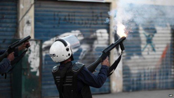 A Bahraini police officer fires tear gas