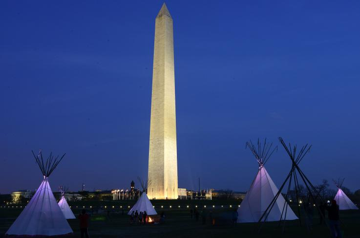 Four tipis and a campfire in the foreground on the National Mall at dusk with the Washington Monument, an obelisk, lit up in the background.