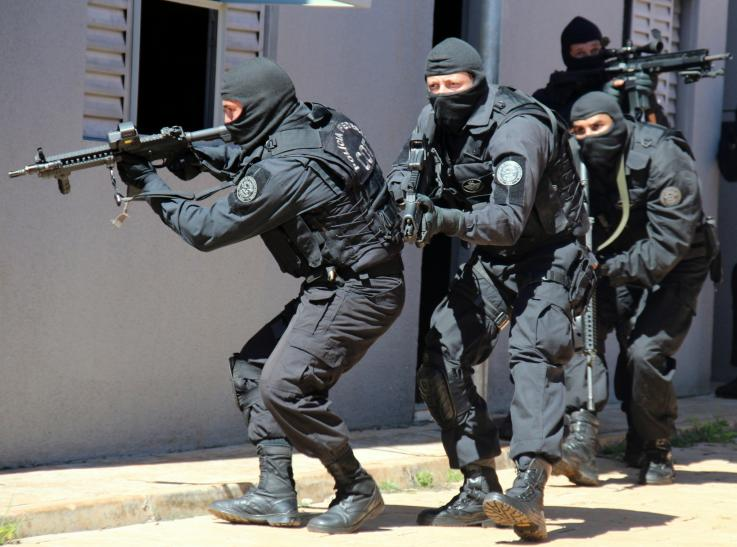 Four police officers wearing balaclavas and pointing in several directions with their machine guns creep round the edge of a building