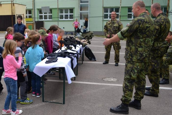 Soldiers talk to young children, who are stood in front of a table covered with guns.