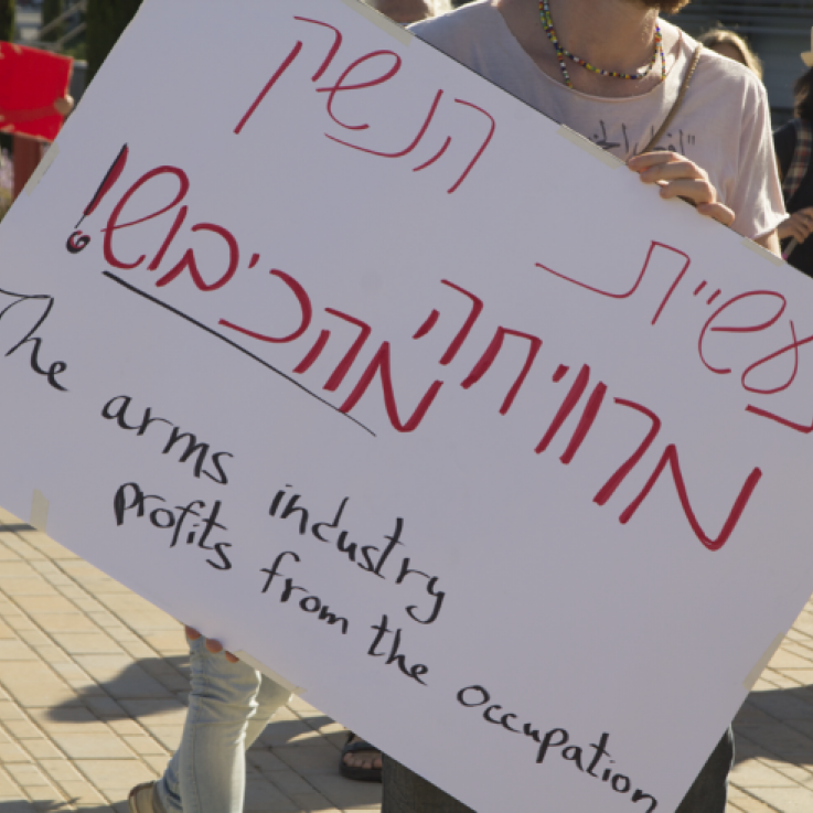 "A protester outside the ISDEF arms fair holds a sign reading ""The arms industry profits from the occupation"""