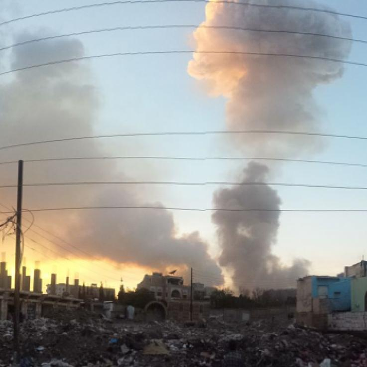 An airstrike in Sana'a, Yemen, in 2015. A cloud of smoke rises from behind buildings. The sun is rising to the left of the picture.